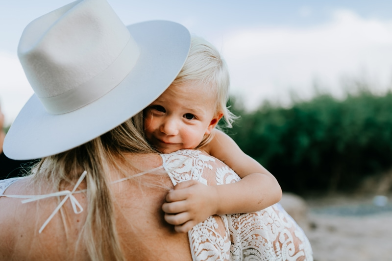 family photography, a young boy smiles as his mother holds him to her shoulder outdoors