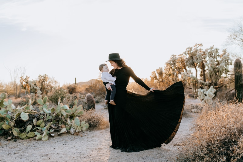 Family Photographer, a young woman in a black flowy dress holds her baby in the desert