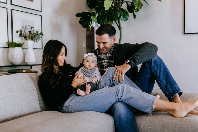 Family Photographer, A husband and wife hold their small baby as they sit on the couch at home