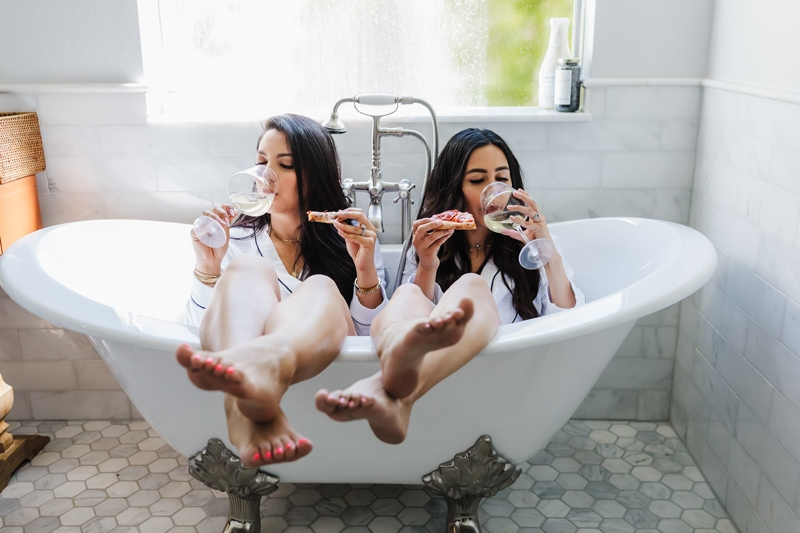 Family Photography, two women sit in a tub sipping wine