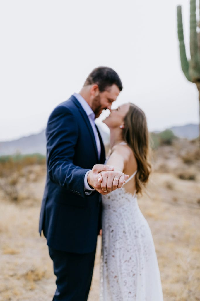 Wedding Photographer, a bride and groom draw close in the desert as if dancing, her ring is on display