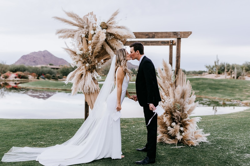 Wedding Photographer, A bride and groom kiss outdoors after their their wedding