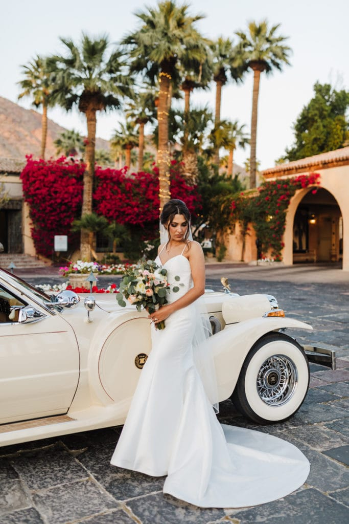 Wedding Photography, A bride stands outside near an old Rolls Royce near a resort