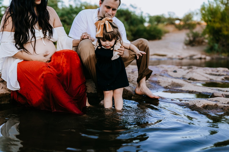 Family Photographer, Man and woman sit at a quiet river bank holding their daughter as she walks in